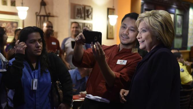 U.S. Democratic presidential candidate Hillary Clinton smiles for a photograph as she greets workers in the employee dinning room at the Rio Hotel and Casino in Las Vegas, Nevada February 18, 2016. REUTERS/David Becker