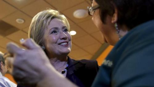 U.S. Democratic presidential candidate Hillary Clinton greets a worker in the employee dinning room at the Rio Hotel and Casino in Las Vegas, Nevada February 18, 2016. REUTERS/David Becker