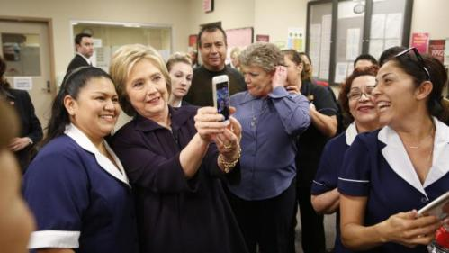Democratic presidential candidate Hillary Clinton takes a selfie with an employee of Paris Las Vegas during a visit to the hotel and casino Thursday, Feb. 18, 2016, in Las Vegas. (AP Photo/John Locher)