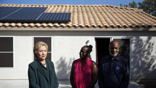 Democratic presidential candidate Hillary Clinton, left, visits with Vicki Early, center, and Tyrone Hych at their home Friday, Feb. 19, 2016, in Las Vegas. Early and Hych have solar power at their home. (AP Photo/John Locher)