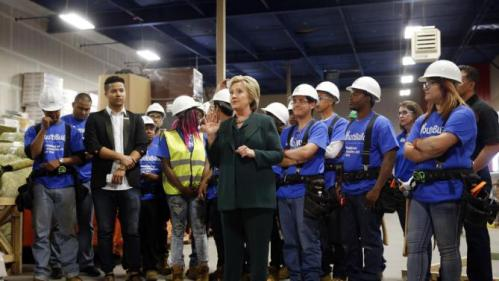 Democratic presidential candidate Hillary Clinton, center, visits a Youthbuild program Friday, Feb. 19, 2016, in Las Vegas. Youthbuild helps low-income young people learn construction skills. (AP Photo/John Locher)