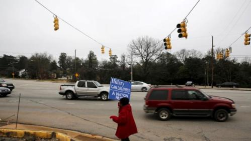 "Viola Rocker holds a sign reading ""Hillary can deliver"" on a sidewalk near where U.S. Democratic presidential candidate Hillary Clinton will hold a town hall meeting at Central Baptist Church in Columbia, South Carolina February 23, 2016. REUTERS/Jonathan Ernst"