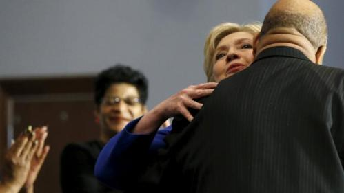 U.S. Democratic presidential candidate Hillary Clinton (2nd R) gets a hug as she takes the stage for a town hall meeting at Central Baptist Church in Columbia, South Carolina February 23, 2016. REUTERS/Jonathan Ernst