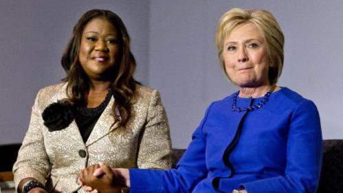 Democratic presidential candidate Hillary Clinton, right, holds hands with Sybrina Fulton, mother of Trayvon Martin, as she reacts to Fulton's statement during a rally at the Central Baptist Church in Columbia, S.C., on Tuesday, Feb. 23, 2016. Clinton spoke and then heard from mothers of victims of gun violence. (AP Photo/Jacquelyn Martin)