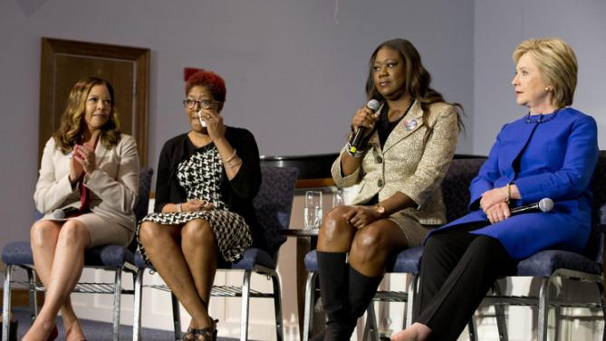 Lucia McBath, left, mother of Jordan Davis, and Maria Hamilton, mother of Dontre Hamilton, react as Sybrina Fulton, mother of Trayvon Martin, talks about her son next to Democratic presidential candidate Hillary Clinton during a rally at the Central Baptist Church in Columbia, S.C., on Tuesday, Feb. 23, 2016, with mothers of victims of gun violence. (AP Photo/Jacquelyn Martin)