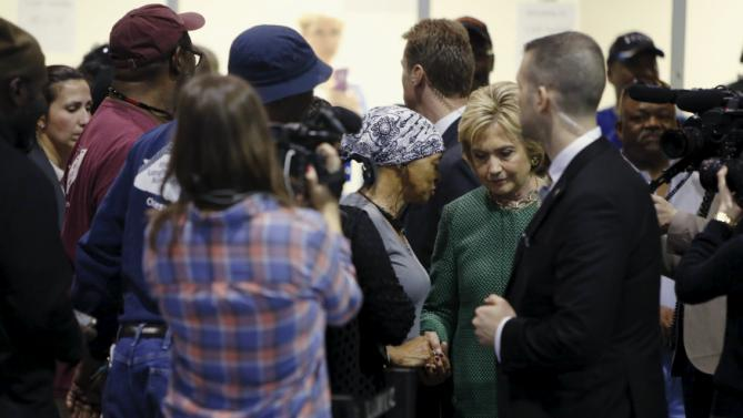 U.S. Democratic presidential candidate Hillary Clinton (R) holds hands with a supporter at the International Longshoremen's Association Local 1422 in Charleston, South Carolina February 24, 2016. REUTERS/Jonathan Ernst