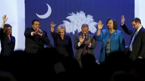 U.S. Democratic presidential candidate Hillary Clinton (3rd L) holds her hand up in prayer with local officials after a town hall meeting for supporters at Royal Baptist Church Family Life Center in North Charleston, South Carolina February 25, 2016. REUTERS/Jonathan Ernst