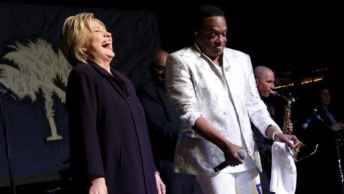 Democratic U.S. presidential candidate Hillary Clinton (L) joins singer Charlie Wilson on stage during a get-out-the-vote concert in support of her at the Music Farm in Charleston, South Carolina February 25, 2016. REUTERS/Jonathan Ernst