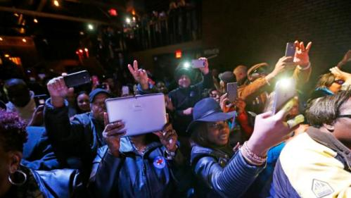 """Audience members take photos and cheer as Democratic presidential candidate Hillary Clinton appears onstage with recording artist Charlie Wilson during a """"Get Out The Vote"""" concert at The Music Farm in Charleston, S.C., Thursday, Feb. 25, 2016. (AP Photo/Gerald Herbert)"""