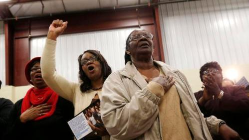 An audience member cheers as the other holds her hand to her heart at the conclusion of National Anthem, as Democratic presidential candidate Hillary Clinton arrives to speak at a campaign event at the Williamsburg County Recreation Center in Kingstree, S.C., Thursday, Feb. 25, 2016. (AP Photo/Gerald Herbert)