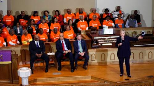 Democratic presidential candidate Hillary Clinton speaks at a campaign event at the Cumberland United Methodist Church in Florence, S.C., Thursday, Feb. 25, 2016. Seated, left to right, are Rev. Anthony Hodge, pastor of the Cumberland United Methodist Church, Sen. Corey Booker, D-N.J., and Dan Gross, president of the Brady Campaign and Center to Prevent Gun Violence. (AP Photo/Gerald Herbert)
