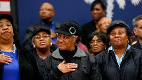 An audience member holds her hand to her heart during the singing of National Anthem, as Democratic presidential candidate Hillary Clinton arrives to speak at a campaign event at the Williamsburg County Recreation Center in Kingstree, S.C., Thursday, Feb. 25, 2016. (AP Photo/Gerald Herbert)