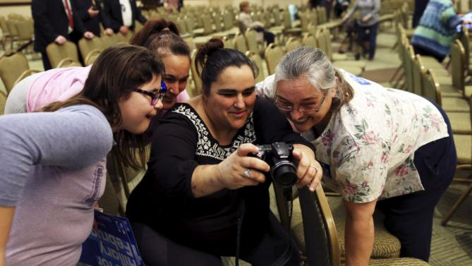 A family looks over photos after a rally for U.S. Democratic presidential candidate Hillary Clinton at the Myrtle Beach Convention Center in Myrtle Beach, South Carolina, February 25, 2016. REUTERS/Randall Hill