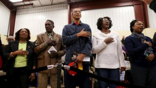 People sing the national anthem before a speech by U.S. Democratic presidential candidate Hillary Clinton at the Williamsburg County Recreation Center in Kingstree, South Carolina, February 25, 2016. REUTERS/Randall Hill
