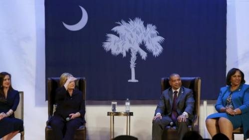 U.S. Democratic presidential candidate Hillary Clinton (2nd L), onstage with local officials, looks into the audience to be able to see a person asking a question during a town hall meeting with supporters at Royal Baptist Church Family Life Center in North Charleston, South Carolina February 25, 2016. REUTERS/Jonathan Ernst