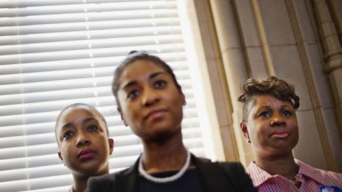 From left, Tanisha Weaver, Karla Johnson and Pamela Carter watch as Democratic presidential candidate, Hillary Clinton speaks at a campaign event at the Old City Council Chambers in City Hall Friday, Feb. 26, 2016, in Atlanta. (AP Photo/David Goldman)