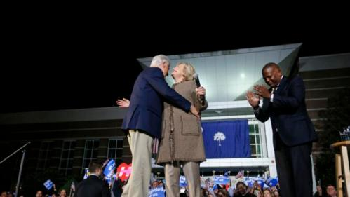 "Democratic presidential candidate Hillary Clinton and her husband, former President Bill Clinton, hug as they arrive to speak at a ""Get Out The Vote Rally"" in Columbia, S.C., Friday, Feb. 26, 2016. Right is Columbia Mayor Stephen K. Benjamin. (AP Photo/Gerald Herbert)"