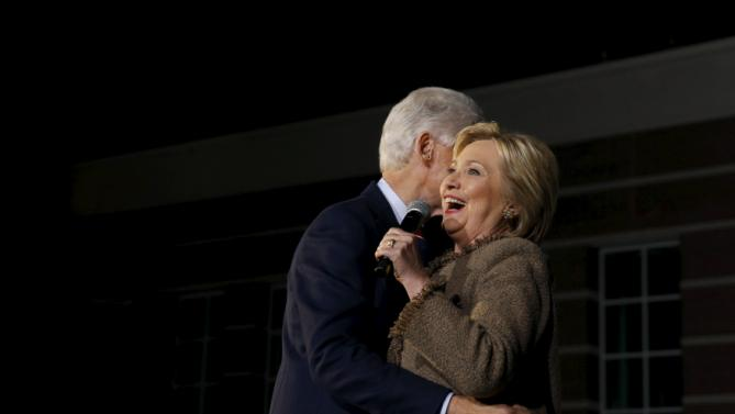Former U.S. President Bill Clinton (L-R) hugs his wife Democratic U.S. presidential candidate Hillary Clinton as she rallies with supporters at an outdoor plaza in Columbia, South Carolina February 26, 2016. REUTERS/Jonathan Ernst