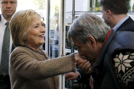Saffron Cafe and Bakery owner Ali Rahnamoon (R) kisses the hand of U.S. Democratic Presidential candidate Hillary Clinton as she arrives to greet voters at his cafe in Charleston, South Carolina, February 26, 2016. REUTERS/Jonathan Ernst