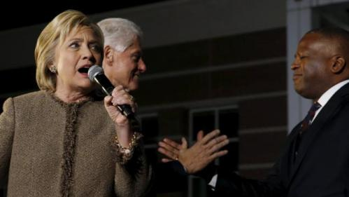 Former U.S. President Bill Clinton (2nd L) and Columbia, South Carolina, Mayor Stephen Benjamin campaign for Democratic U.S. presidential candidate Hillary Clinton (L) as she rallies with supporters at an outdoor plaza in Columbia, South Carolina February 26, 2016. REUTERS/Jonathan Ernst
