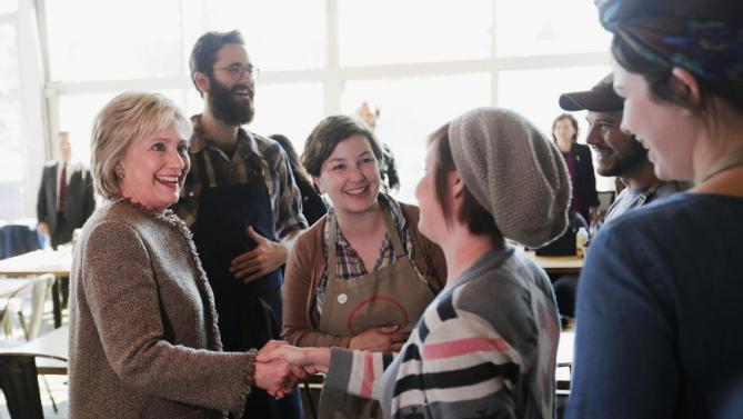 Democratic presidential candidate Hillary Clinton greets workers Whitney Gomez, right, Michael Harrell, left, and Sarah O'Brien, center, while visiting Octane Coffee, Friday, Feb. 26, 2016, in Atlanta. (AP Photo/David Goldman)