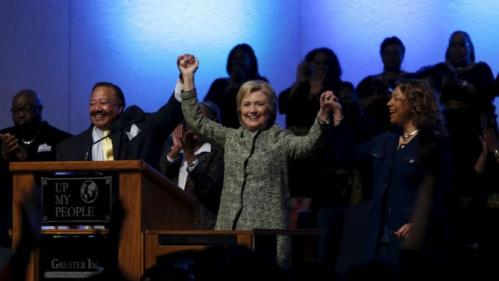 U.S. Democratic presidential candidate Hillary Clinton raises her arms with pastor Bill Adkins (L) after speaking during a church service at the Greater Imani Cathedral of Faith in Memphis, Tennessee, February 28, 2016. REUTERS/Jonathan Ernst