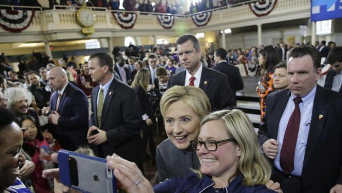 Democratic presidential candidate Hillary Clinton is surrounded by security as she poses for a photo with a supporter at a campaign event at the Old South Meeting House, Monday, Feb. 29, 2016, in Boston. (AP Photo/Elise Amendola)