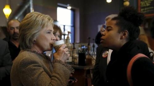 U.S. Democratic presidential candidate Hillary Clinton has an exchange with a young woman asking questions about issues pertaining to the Somali-American community as she greets people at Mapps Coffee in Minneapolis, Minnesota March 1, 2016. REUTERS/Jonathan Ernst