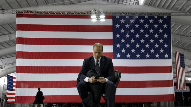 A Hillary Clinton campaign volunteer checks his phone before the start of a rally for the Democratic presidential candidate, Wednesday, March 2, 2016, in New York. (AP Photo/Julie Jacobson)