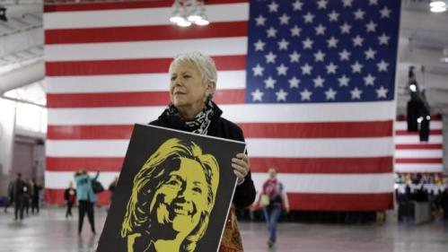 Campaign volunteer Leila Walsh of Jersey City, N.J., stands near an entrance to the Jacob Javits Center to greet supporters as they arrive before the start of a rally for Democratic presidential candidate Hillary Clinton, Wednesday, March 2, 2016, in New York. (AP Photo/Julie Jacobson)