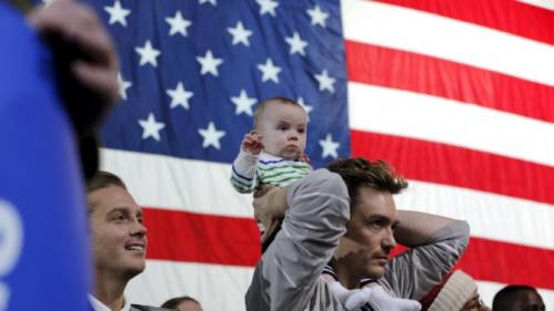 A man holds his child on his shoulders as they wait for U.S. presidential candidate and former Secretary of State Hillary Clinton to address a Hillary for America rally in New York March 2, 2016. REUTERS/Lucas Jackson