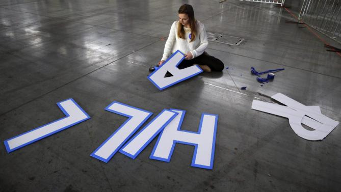 A campaign volunteer lines letters of Democratic presidential candidate Hillary Clinton's name with blue tape before the start of a rally for Clinton, Wednesday, March 2, 2016, in New York. (AP Photo/Julie Jacobson)