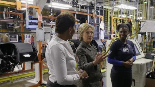 Democratic presidential candidate, Hillary Clinton speaks with Deanne Austin, left, and Victoria Montgomery at the Detroit Manufacturing Systems plant, Friday, March 4, 2016, in Detroit. (AP Photo/Carlos Osorio)