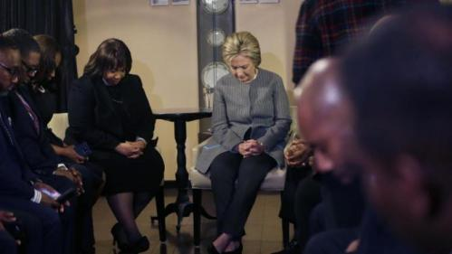 Democratic presidential candidate Hillary Clinton prays with African American ministers, Saturday, March 5, 2016, in Detroit. (AP Photo/Carlos Osorio)