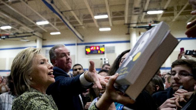Democratic presidential candidate Hillary Clinton reaches for books she is asked to sign as she greets people in the crowd during a campaign event at Sullivan Community Center and Family Aquatic Center in Vernon Hills, Ill., Thursday, March 10, 2016. (AP Photo/Carolyn Kaster)