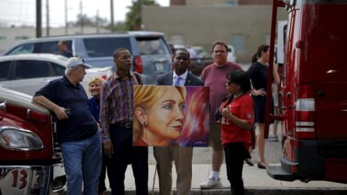 A supporter of Democratic U.S. presidential candidate Hillary Clinton holds a painting of her outside a campaign rally site in Tampa, Florida, March 10, 2016. REUTERS/Carlos Barria EDITORIAL USE ONLY. NO RESALES. NO ARCHIVE