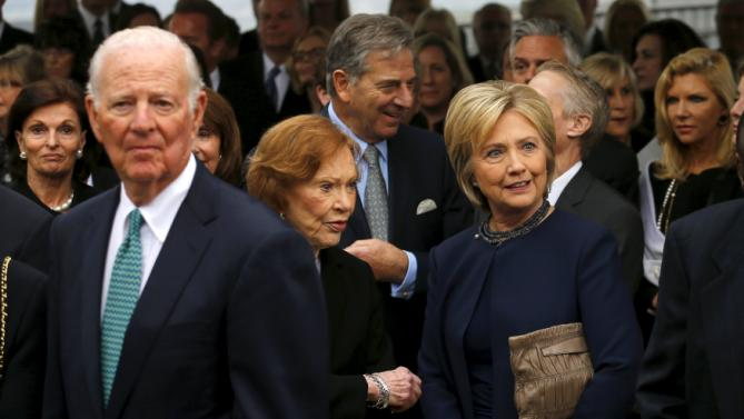 Former secretary of state James Baker (L) waits in a receiving line with former first lady Rosalynn Carter (C) and former first lady Hillary Clinton (R) as they pay their respects during the funeral for former first lady Nancy Reagan at the Ronald Reagan Presidential Library in Simi Valley, California March 11, 2016. REUTERS/Mike Blake