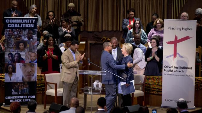 Democratic presidential candidate Hillary Clinton is embraced and greeted by Michael Nelson Sr., President Cleveland Chapter NAACP, second from left, and Rev. Dr. Jawanza Karriem Colvin, left in tan suit, as she come forward to speak during a town hall meeting at Olivet Institutional Baptist Church in Cleveland, Saturday, March 12, 2016. (AP Photo/Carolyn Kaster)
