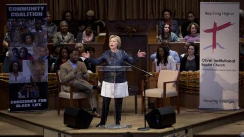 Democratic presidential candidate Hillary Clinton speaks during a town hall meeting at Olivet Institutional Baptist Church in Cleveland, Saturday, March 12, 2016. Seated at left is Rev. Dr. Jawanza Karriem Colvin. (AP Photo/Carolyn Kaster)