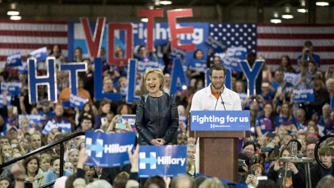 Democratic presidential candidate Hillary Clinton stands on stage as she is introduced by student Nathan Garrett at a campaign event at the Nelson-Mulligan Carpenters' Training Center in St. Louis, Saturday, March 12, 2016. (AP Photo/Carolyn Kaster)