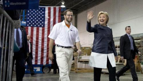 Democratic presidential candidate Hillary Clinton walks with student Nathan Garrett as they arrive at a campaign event at the Nelson-Mulligan Carpenters' Training Center in St. Louis, Saturday, March 12, 2016. (AP Photo/Carolyn Kaster)