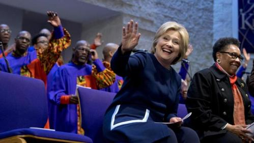 Democratic presidential candidate Hillary Clinton waves as she sits with U.S. Rep. Marcia Fudge, D-Ohio, during service at Mount Zion Fellowship Church in Highland Hills, Ohio, Sunday, March 13, 2016. (AP Photo/Carolyn Kaster)