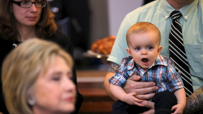 A baby looks at Democratic U.S. Presidential candidate Hillary Clinton as she speaks with local residents during a campaign stop meeting at coffee shop in Marion, Ohio, March 13, 2016. REUTERS/Carlos Barria