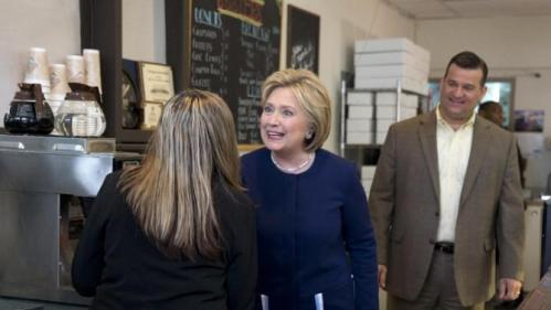 Democratic presidential candidate Hillary Clinton, joined by Marion, Ohio, Mayor Scott Schertzer, right, greets a woman behind the counter as she arrives for a campaign stop at 8 Sisters Bakery in Marion, Ohio, Sunday, March 13, 2016. (AP Photo/Carolyn Kaster)