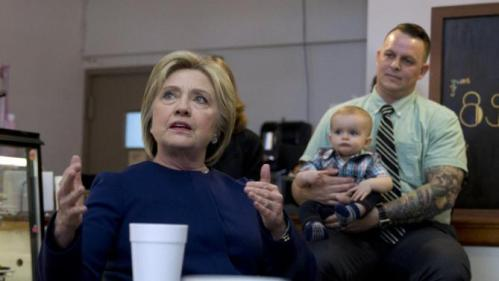 As James Kee holds his baby son, Merric Kee, in the background, Democratic presidential candidate Hillary Clinton talks during a campaign stop at 8 Sisters Bakery in Marion, Ohio, Sunday, March 13, 2016. (AP Photo/Carolyn Kaster)