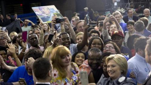 A person on the audience hold up an image of Republican presidential candidate Donald Trump as Democratic presidential candidate Hillary Clinton greets supporters and takes photos during a campaign event at the Grady Cole Center in Charlotte, N.C., Monday, March 14, 2016. (AP Photo/Carolyn Kaster)