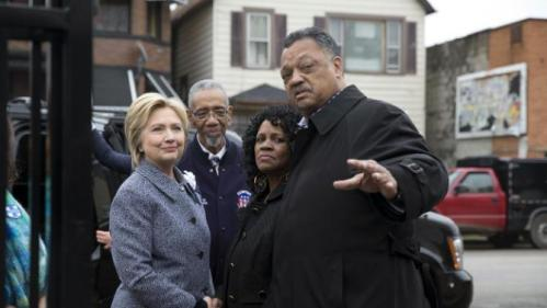 Democratic presidential candidate Hillary Clinton, is greeted by Rev. Jesse Jackson, right, Diane Latiker of Kids off the Block memorial, second from right, and Rep Bobby Rush, D-Ill., as she arrives to visit Kids off the Block memorial l to children killed by gun violence in Chicago, Monday, March 14, 2016. (AP Photo/Carolyn Kaster)