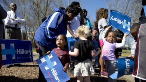 Kids play with campaign signs before Democratic presidential candidate Hillary Clinton arrives to visit a polling place a Southeast Raleigh Magnet High School in Raleigh, N.C., Tuesday, March 15, 2016. (AP Photo/Carolyn Kaster)