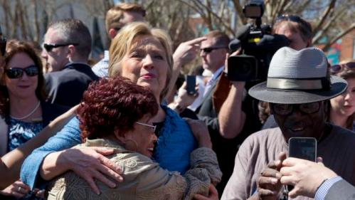Democratic presidential candidate Hillary Clinton hugs a supporter as she visits a polling place a Southeast Raleigh Magnet High School in Raleigh, N.C., Tuesday, March 15, 2016. (AP Photo/Carolyn Kaster)