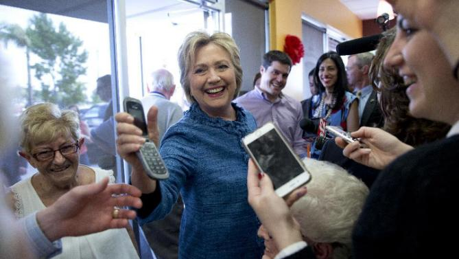 Democratic presidential candidate Hillary Clinton hands a phone back to a woman after speaking to her son as she visits the Dunkin' Donuts in West Palm Beach, Fla., Tuesday, March 15, 2016. Clinton faces Democratic rival Bernie Sanders in primary contests in five states on Tuesday: North Carolina, Florida, Ohio, Missouri and Illinois. (AP Photo/Carolyn Kaster)